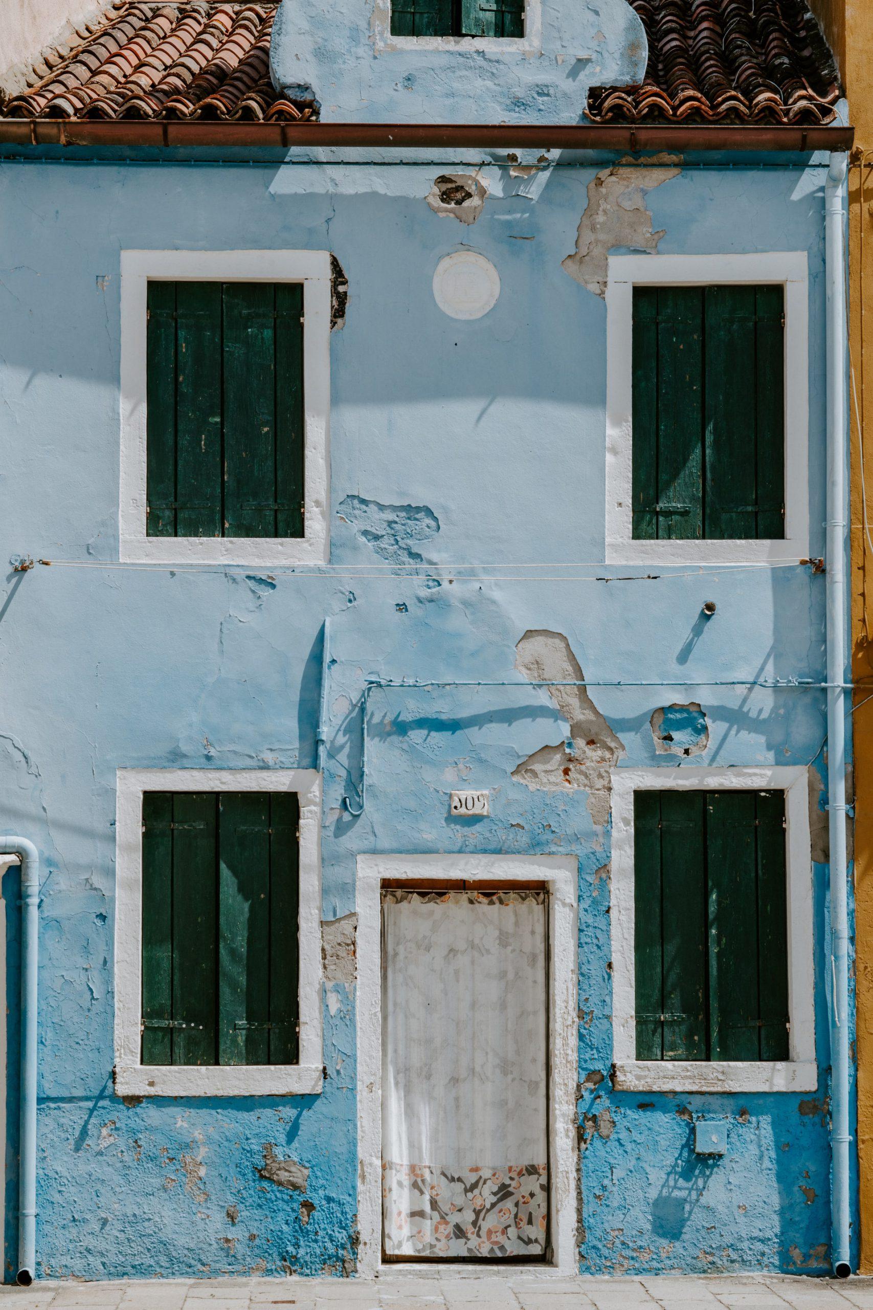 blauw huis met afgebladderde verf
