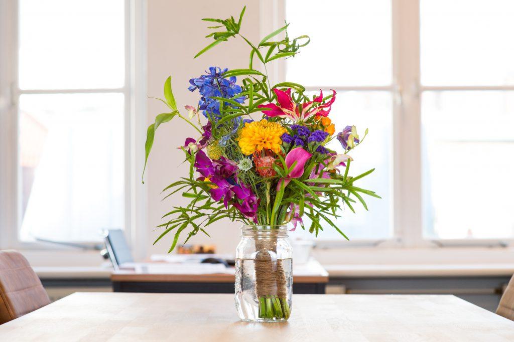 rode, blauwe, gele en paarse bloemen in een vaas